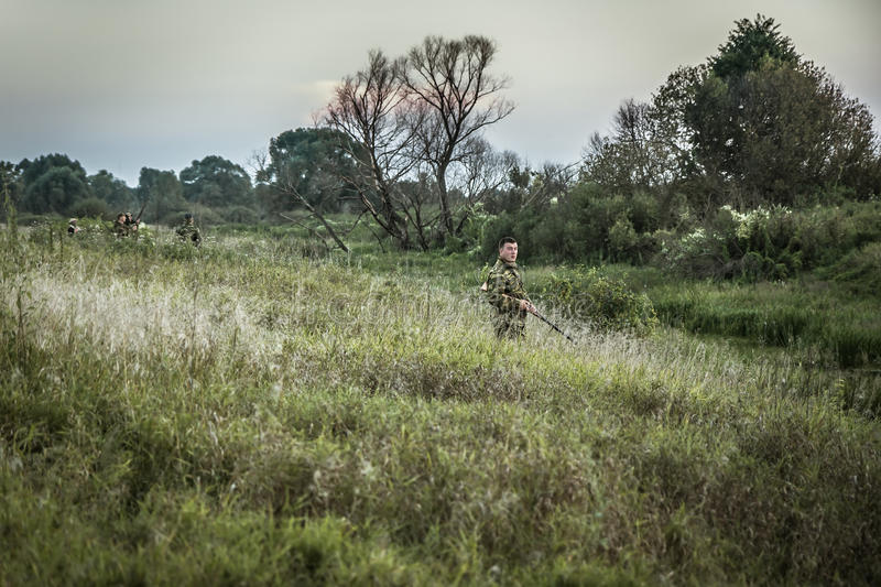Hunter man in camouflage standing in tall grass nearby wetland during hunting stock photography
