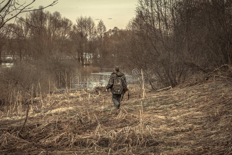 Hunter man creeping forest river during hunting season royalty free stock photography