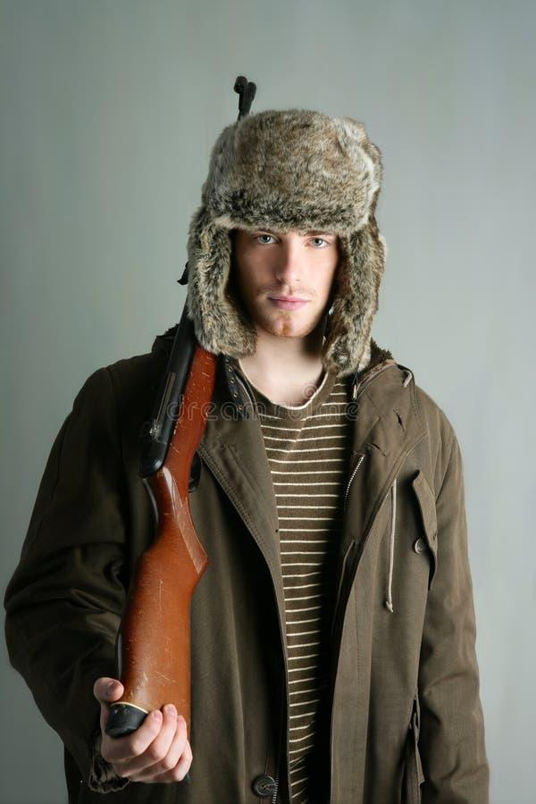 Hunter man fur winter hat holding rifle gun stock photo
