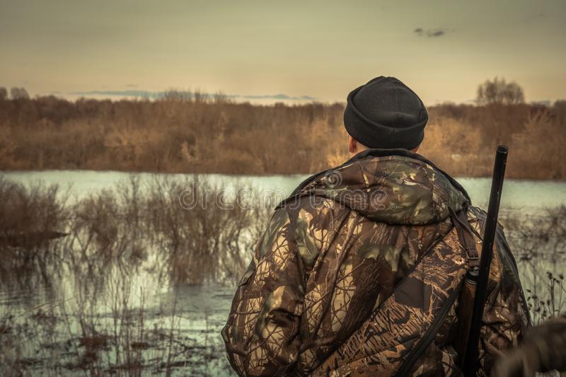 Hunter man hunting looking into the distance horizon in camouflage during hunting season rear view sunset river flood landscape stock photography