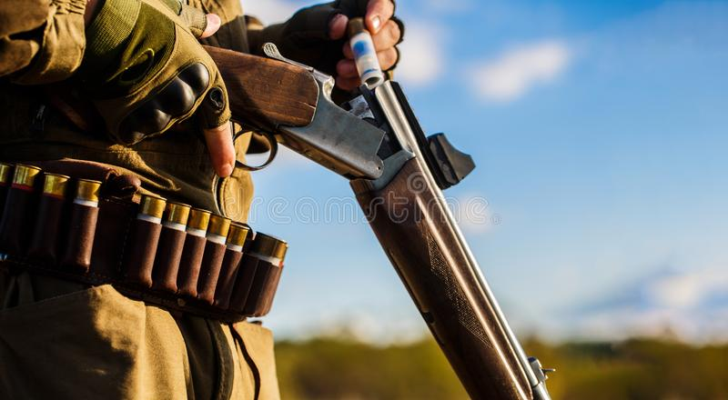 Hunter man. Hunting period. Male with a gun, rifle. Man is charging a hunting rifle. Process of hunting during hunting royalty free stock photography