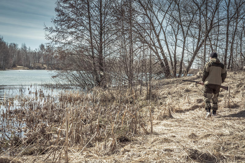 Hunter man walking along river bank during spring hunting season royalty free stock image