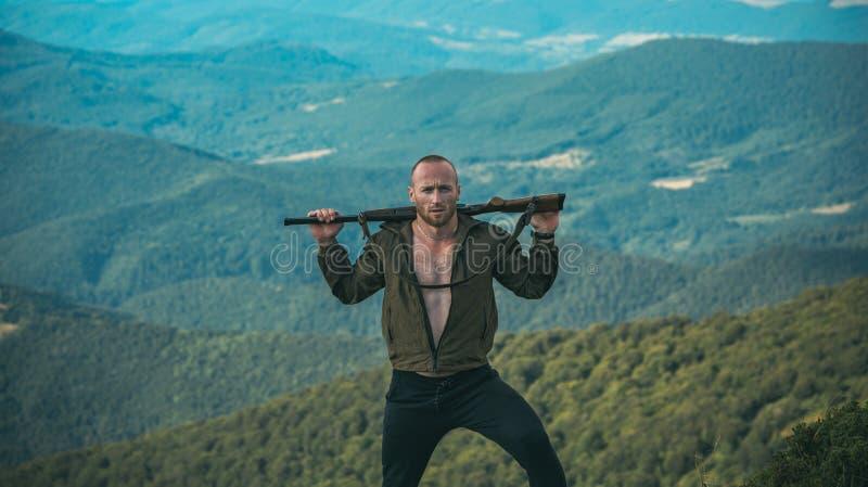 Hunter med sitt gevär Hunter i kamouflage-kläder redo att jaga med jaktgevär Jaktperiod sommarsäsong royaltyfri foto
