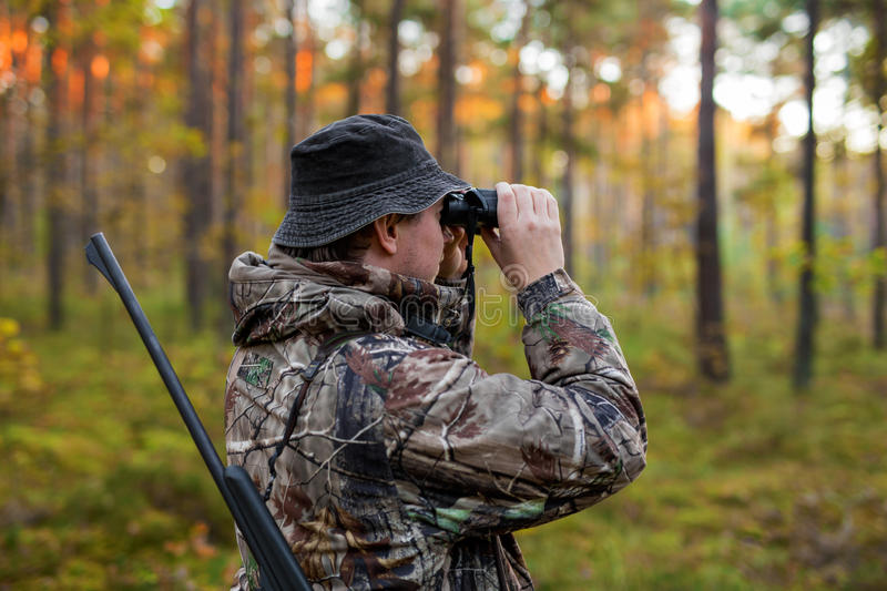 Hunter observing forest with binoculars royalty free stock photos