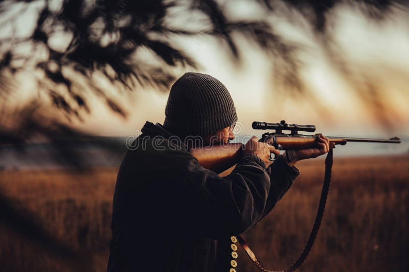 Hunter observing in the wilderness. Hunter observing on field and pointing gun to his prey royalty free stock photos