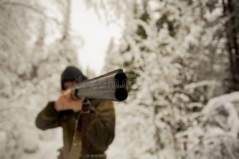 Hunter Pointing a Gun. Hunter is pointing a gun to unseen aim during the hunt in winter forest royalty free stock photography
