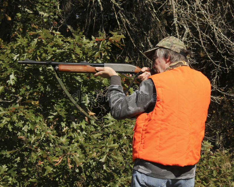 Hunter pointing a shotgun. Hunter in an orange safety vest pointing a shotgun with a forest background royalty free stock photos