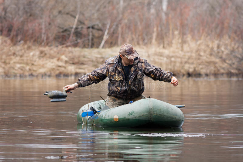 The hunter puts stuffed duck. On water royalty free stock photos