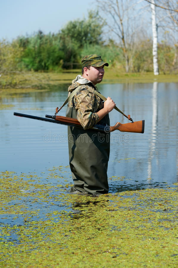 Hunter with rifle gun in bog royalty free stock photo