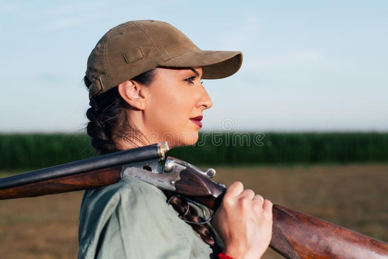 Hunter with a rifle on her shoulder. royalty free stock image