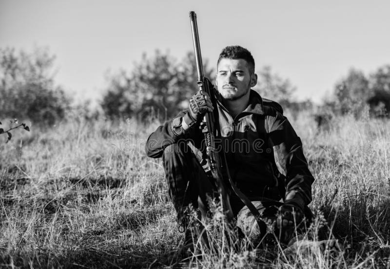 Hunter satisfied with catch relaxing. Rest for real man concept. Hunter with rifle relaxing in nature environment. Tired stock image