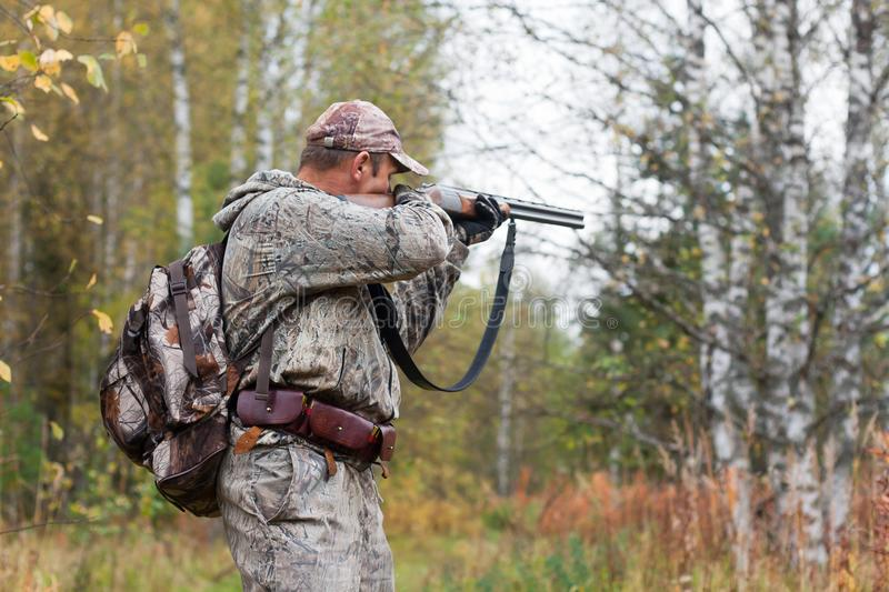 Hunter taking aim from a hunting gun. Hunter in camouflage taking aim from a hunting gun in the wildfowl stock image