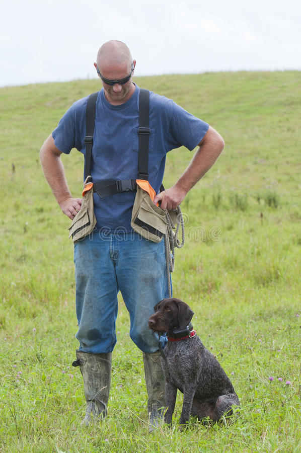 Hunter training his dog. Hunter training his young dog in the late summer stock image