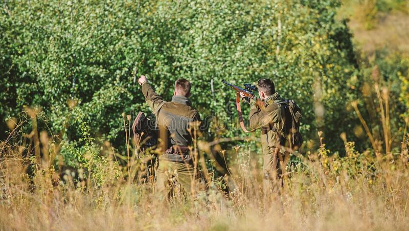 Hunters friends enjoy leisure. Teamwork and support. Activity for real men concept. Hunters with rifles in nature. Environment. Hunters gamekeepers looking for stock image