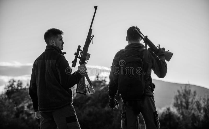 Hunters friends gamekeepers with guns silhouette sky background. Hunters rifles nature environment. That was great day royalty free stock image