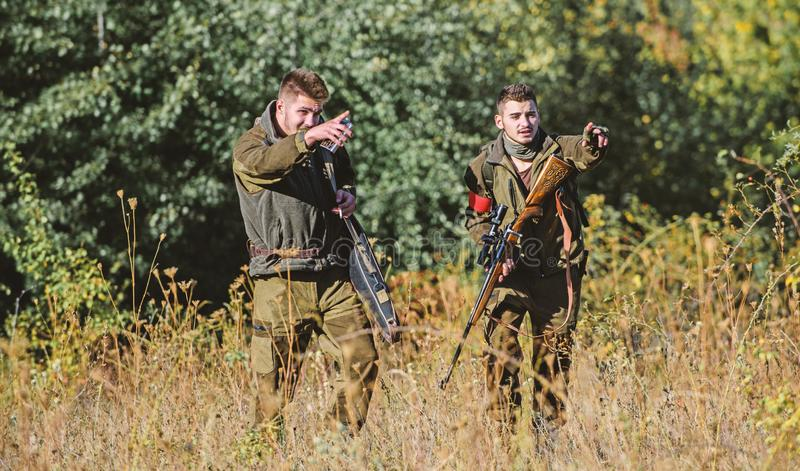 Hunters gamekeepers looking for animal or bird. Hunting with friends. Hunters friends enjoy leisure. Hunters with rifles royalty free stock photo