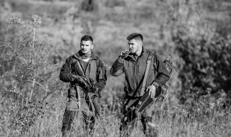Hunters gamekeepers looking for animal or bird. Illegal hunting. Hunters friends enjoy leisure. Hunters with rifles in stock photography