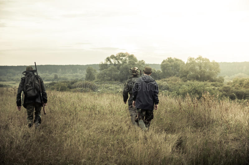 Hunters going on rural field at sunrise during hunting season royalty free stock photo