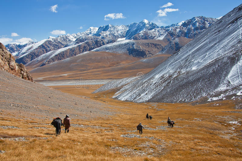 Hunters with horses descend from the mountains into the valley. stock image
