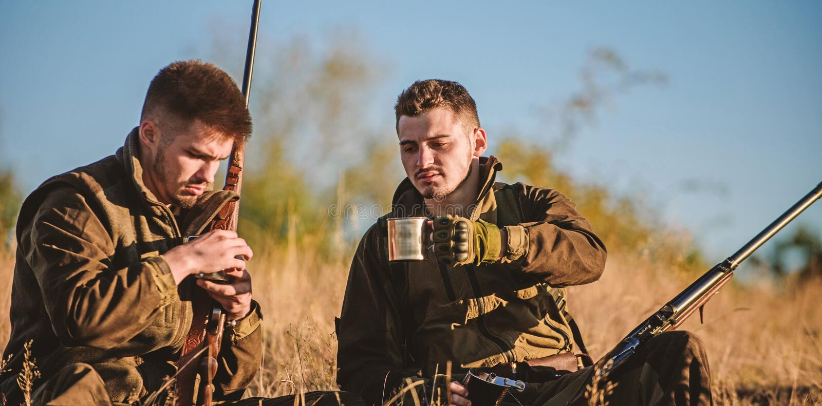 Hunters with rifles relaxing in nature environment. Hunters friends enjoy leisure. Hunting with friends hobby leisure stock photography