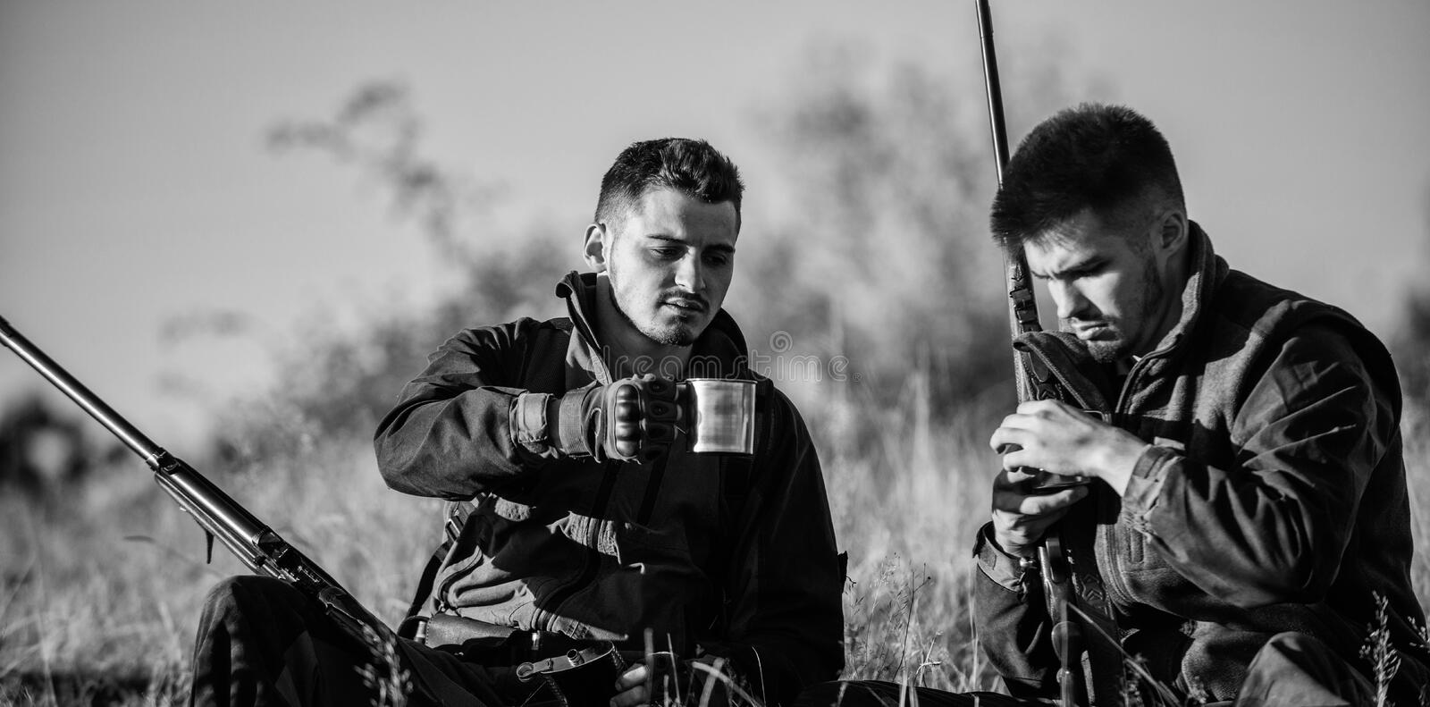 Hunters with rifles relaxing in nature environment. Hunters friends enjoy leisure. Hunting with friends hobby leisure royalty free stock photo