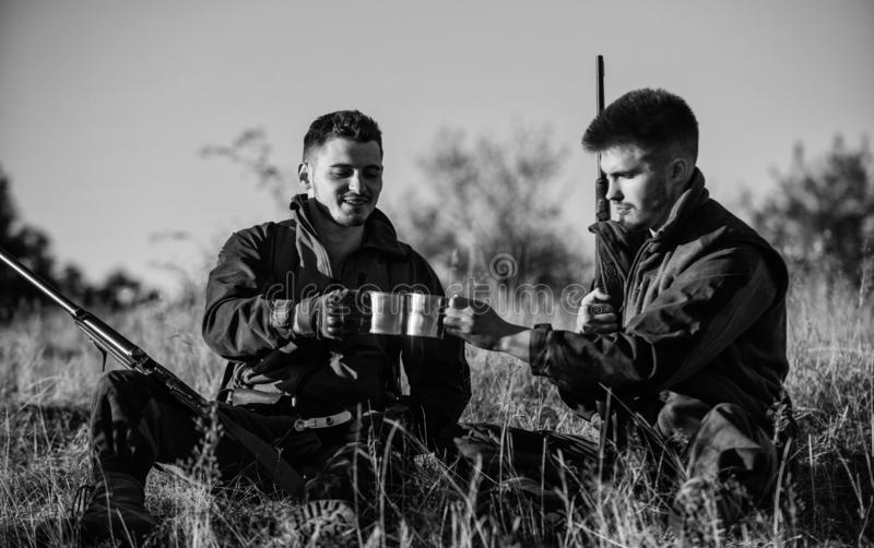 Hunters with rifles relaxing in nature environment. Hunter friend enjoy leisure in field. Hunting with friends hobby stock photo