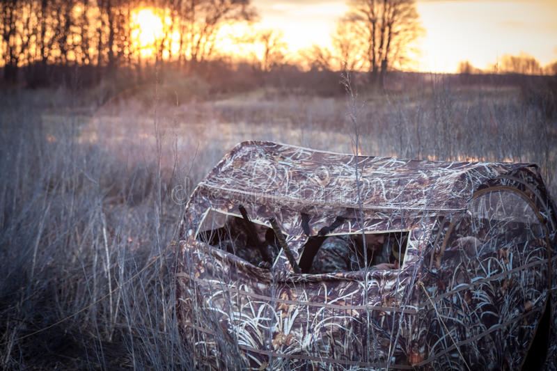 Hunters waiting for prey in hunting tent in reed bushes next to the river during sunrises. stock photos
