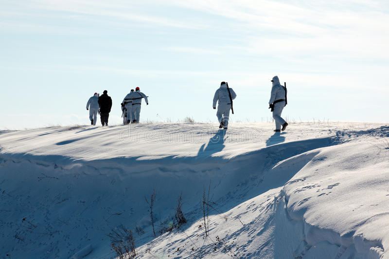 Hunters walking in snow stock photos
