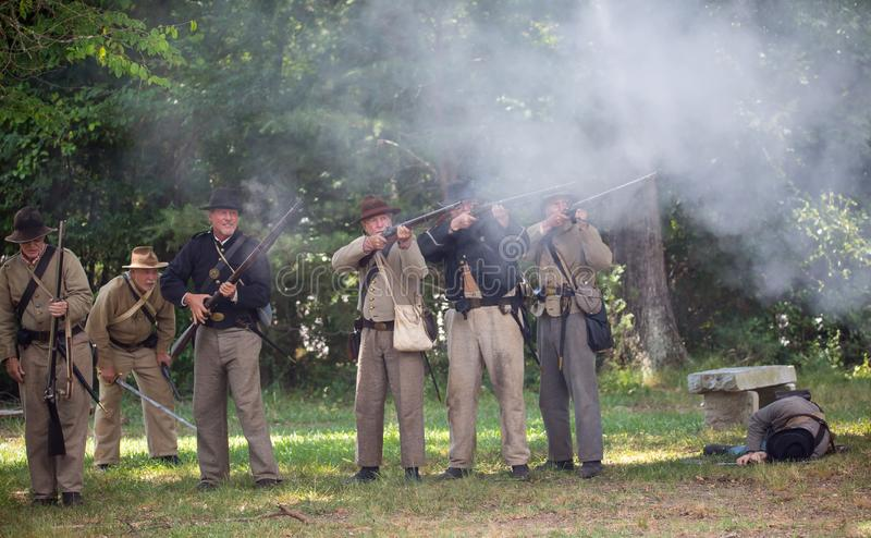 American Civil War Battle Reenactment. HUNTERSVILLE, NC - JUNE 1, 2019 USA:  Reenactors in Confederate army uniforms fire a rifle volley during an American Civil stock images