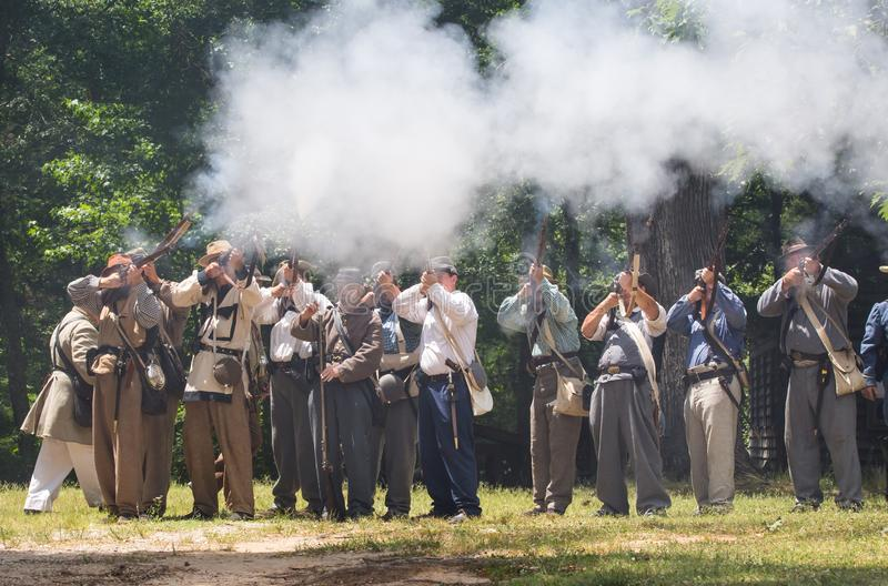 American Civil War Battle Reenactment. HUNTERSVILLE, NC - JUNE 1, 2019 USA:  Reenactors in Confederate army uniforms fire a rifle volley during an American Civil stock photos