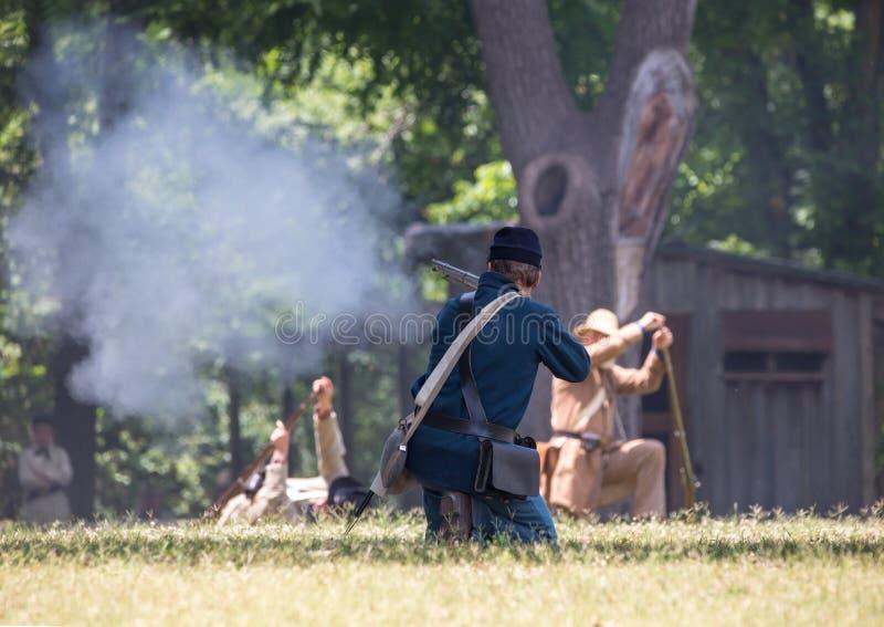 American Civil War Battle Reenactment. HUNTERSVILLE, NC - JUNE 1, 2019 USA:  Reenactors in Confederate and Union army uniforms recreate an American Civil War stock photo