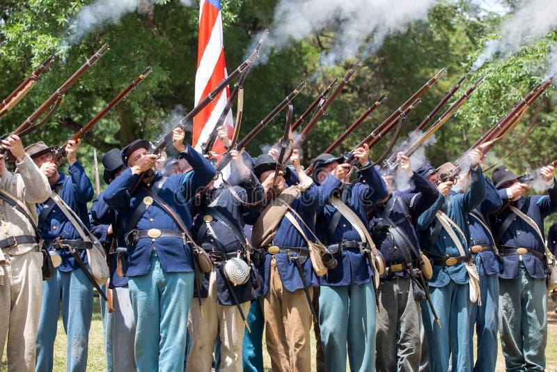 American Civil War Battle Reenactment. HUNTERSVILLE, NC - JUNE 1, 2019 USA:  Reenactors in Union army uniforms fire a rifle salute during an American Civil War royalty free stock image