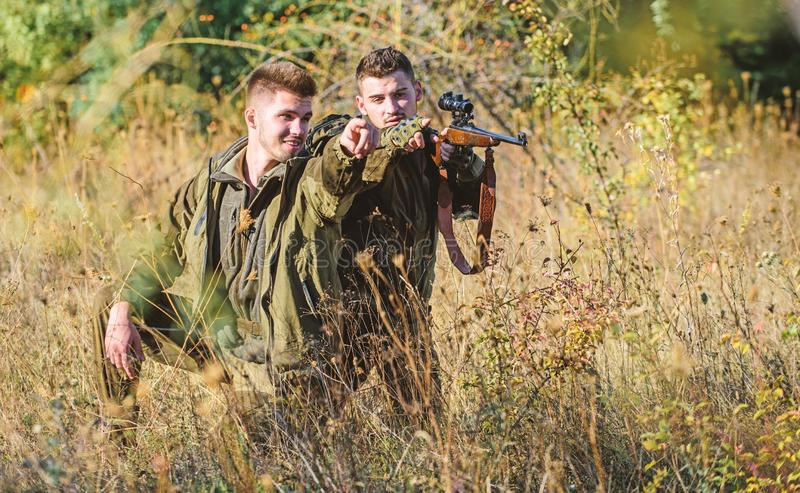 Hunting with friends hobby leisure. Hobby for real men concept. Hunters with rifles in nature environment. Hunter friend royalty free stock photo