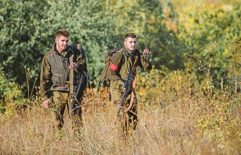 Hunting with friends. Hunters friends enjoy leisure. Hunters with rifles in nature environment. Teamwork and support stock photography