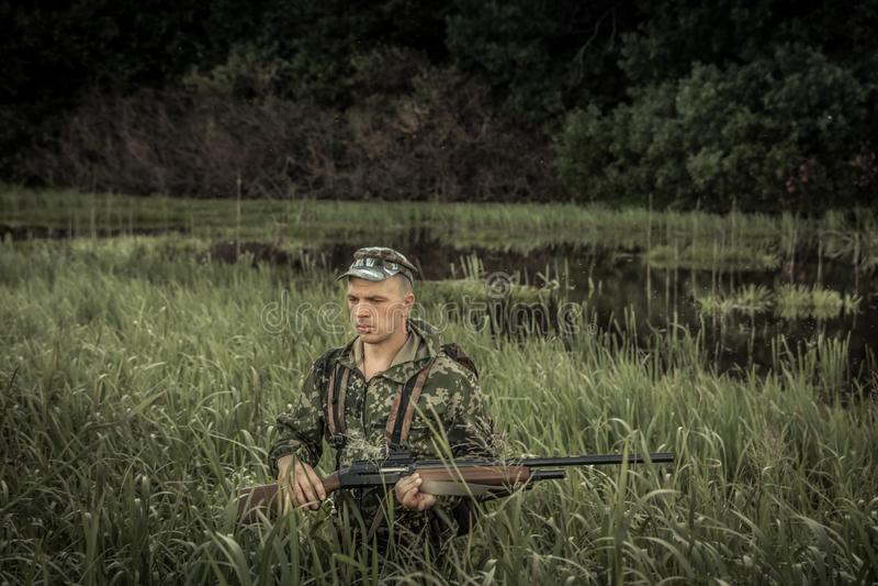 Hunting hunter brutal man breaking through swamp tall grass during hunting season stock photography
