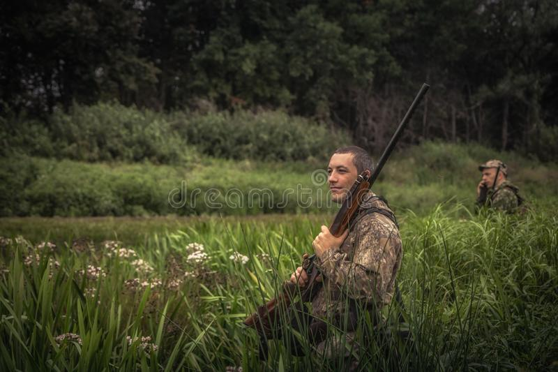 Hunting hunter men with gun hiding in tall grass during hunting season royalty free stock photos