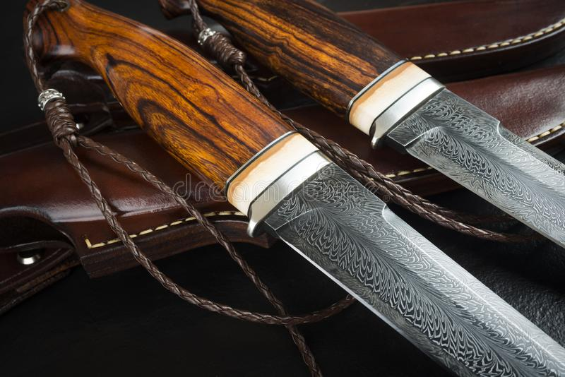 Hunting knife from Damascus mosaic on a wooden background. Leather Sheath Handmade.  stock photography