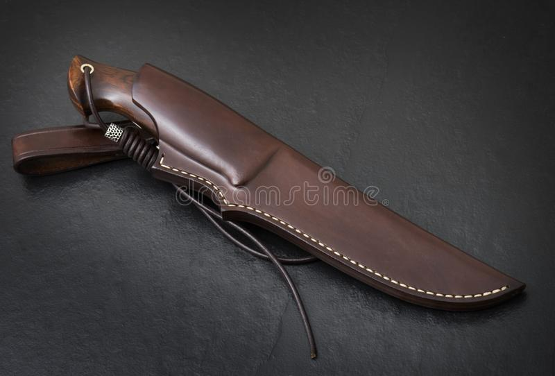 Hunting knife handmade on a black background. Leather Sheath Handmade.  stock images