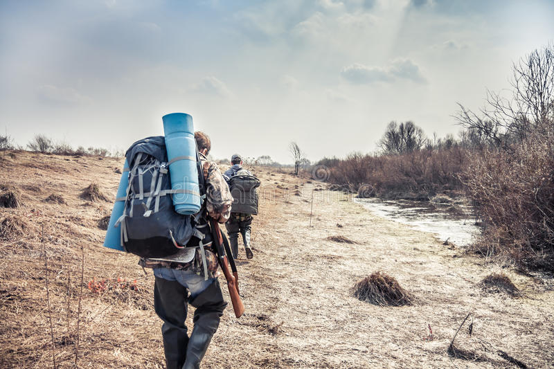 Hunting scene with hunters with backpack and hunting equipment going across rural area during hunting season stock photography