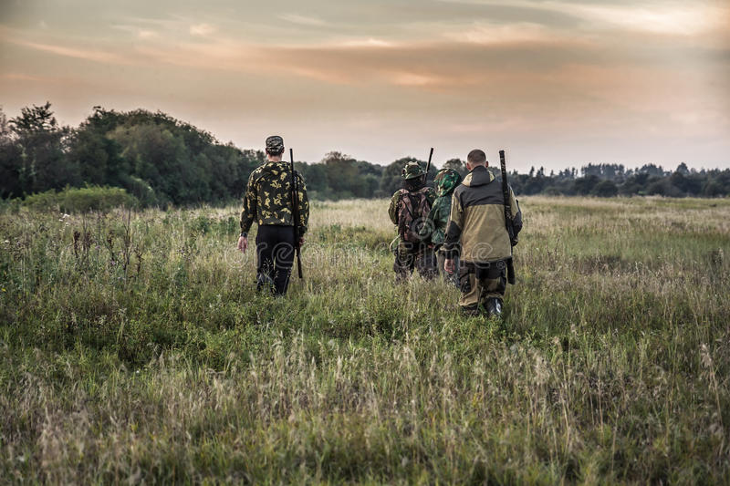 Hunting scene with hunters going through rural field during hunting season in overcast day during sunset with moody sky stock photography