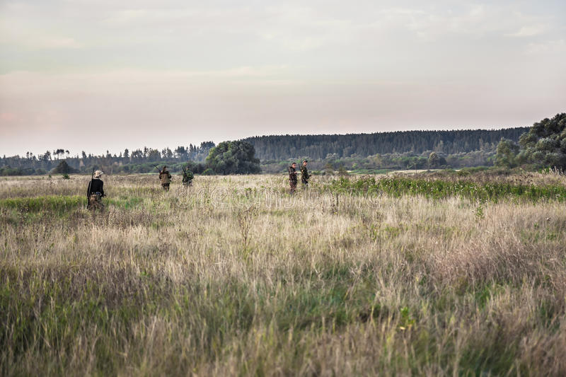 Hunting scene with hunters going through rural field during hunting season royalty free stock photos