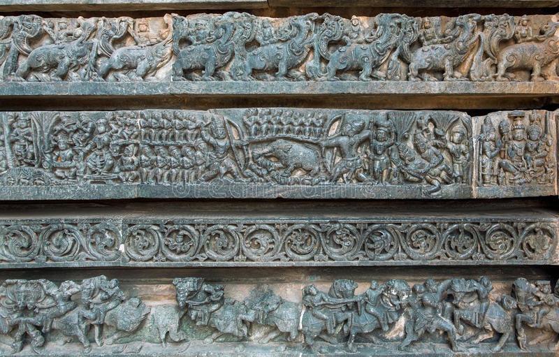 Hunting scene and other stone artworks on background sculptures. Mythical patterns of temple in Halebidu, India stock images