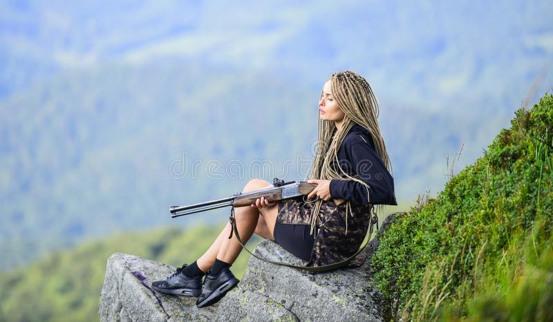 Hunting season. Hunter mountains landscape background. Sexy warrior. Aiming concept. Amazon girl sit on cliff prepare. Gun for hunting. Woman attractive long stock images
