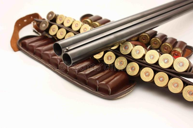 Hunting shotgun barrel and cartridges. An image showing a double barreled hunting shotgun, with a cartridge ammo belt, with a white background royalty free stock image