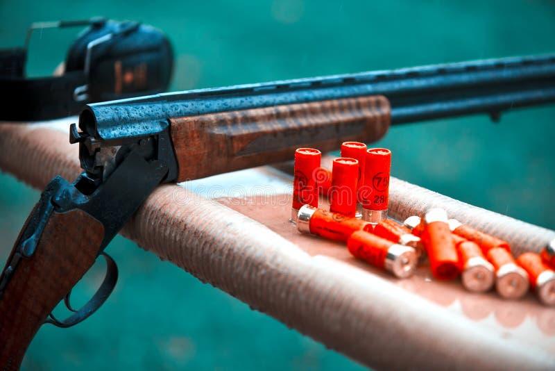 Hunting shotgun with bullets cartridges drop rain. smoke. Hunting shotgun with bullets cartridges drop rain royalty free stock photos