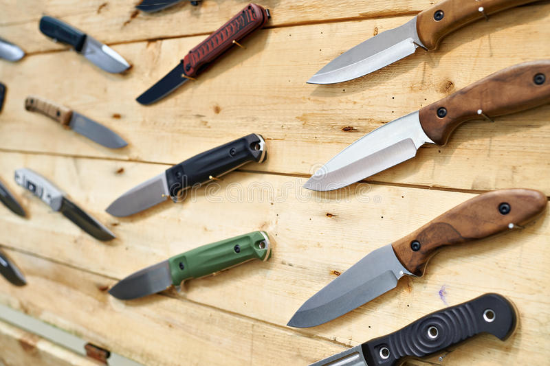 Hunting and tactical knives on wooden stand in store. Hunting and tactical knives on a wooden stand at an exhibition in the store royalty free stock image