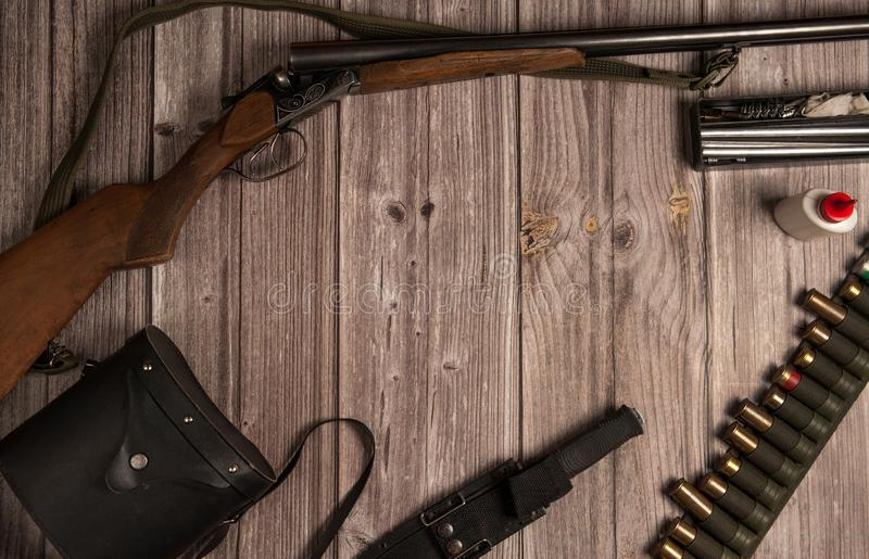 The frame is made of hunting weapons, a bandoleer with cartridges, binoculars in a case, a knife in a sheath, equipment for cleani stock images