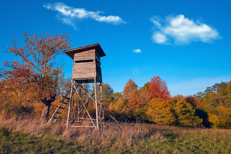 Hunting tower in wild forest. Wooden Hunter Hide High watch post tower. Hunter`s observation point in forest in Europe.  royalty free stock photos