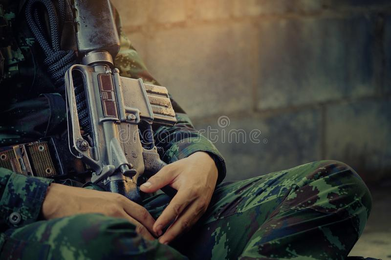 Hunting, war, army and people concept - young soldier, ranger or. Hunter with gun sitting and sleeping, Soldier sits near a brick wall stock image