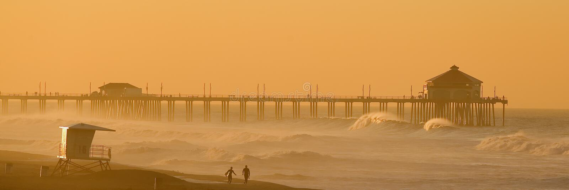 Huntington Beach at Dawn. Two Surfers walk along the Beach in Huntington Beach at Dawn stock image
